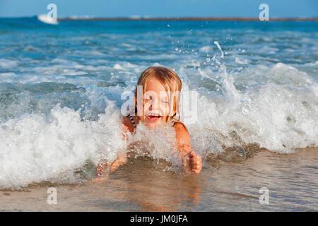Vie de famille heureuse. Baby Girl splashing et sauter avec plaisir dans les vagues déferlantes. Billet d'été, de Banque D'Images