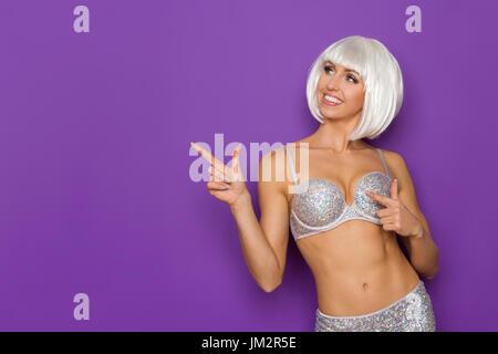 Fit sourire jeune femme en perruque platine et argent bra pointant et à la voiture. Waist up studio shot sur fond Banque D'Images
