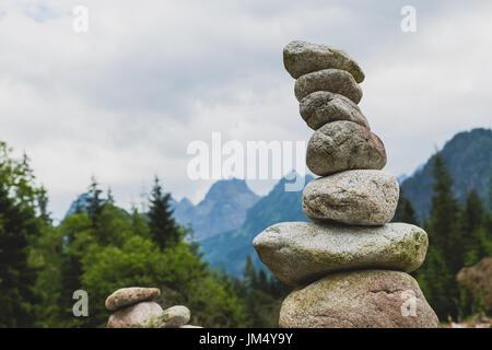 L'équilibre des pierres, hiérarchie pile ciel nuageux en montagne. Concept de stabilité d'inspiration sur les rochers. Banque D'Images