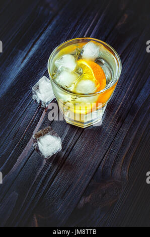 Cocktail glacé à l'orange, tonique, de la vodka et de la glace sur fond sombre bois