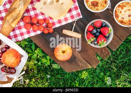 Photo prise à la verticale de l'aire de pique-nique avec des pommes, des fruits dans un contenant de plastique, Banque D'Images