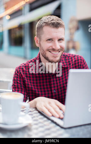 Portrait of Young Man at Outdoor Cafe Working On Laptop Banque D'Images