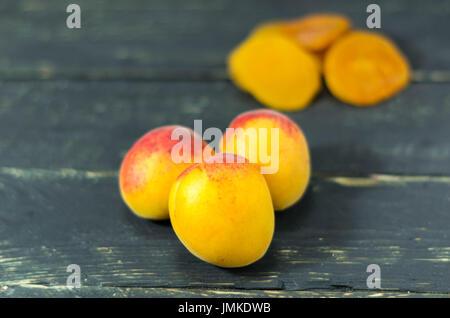 Abricot frais et abricots secs. Fond en bois sombre. En bonne santé. Banque D'Images