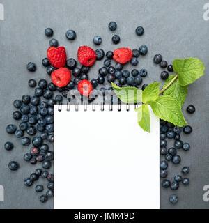 Les bleuets, framboises, menthe et le bloc-notes de la rédaction de notes ou de résolutions, concept de l'alimentation, Banque D'Images