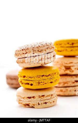 Certaines cheminées de macarons appétissants avec différentes saveurs et couleurs sur un fond blanc Banque D'Images