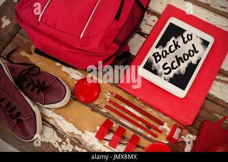 Retour à l'école texte sur pink splash contre high angle view de sac avec des chaussures sur la table et tablette Banque D'Images