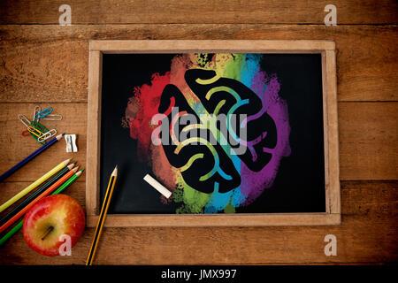 L'image graphique de cerveau sur splash coloré contre Vue de dessus de tableau noir avec apple et crayons Banque D'Images