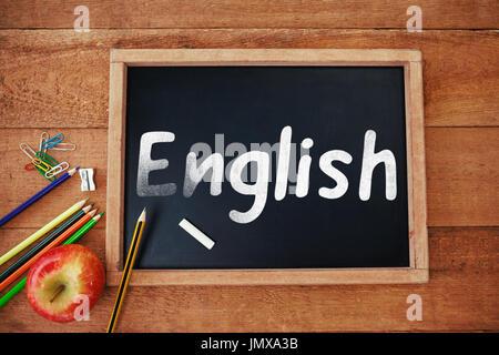 Texte anglais sur fond blanc contre Vue de dessus de tableau noir avec apple et crayons Banque D'Images