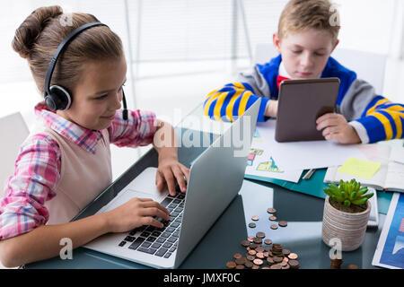 Portrait d'enfants comme des cadres d'affaires travaillant ensemble dans office Banque D'Images