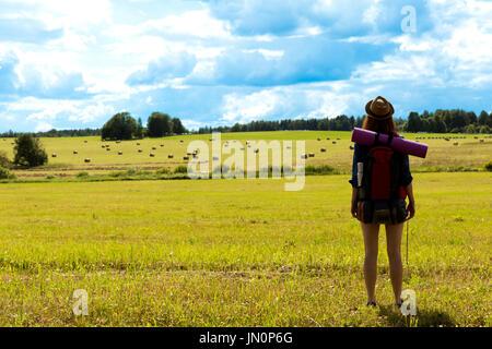 Jeune femme avec sac à dos en randonnée dans la campagne environnante. Concept de voyage sans stress. Banque D'Images