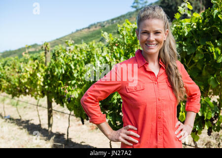 Portrait of smiling woman standing with hands on hip in vineyard Banque D'Images