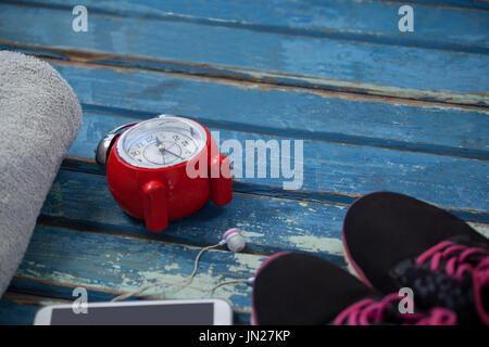Portrait de réveil par téléphone mobile au milieu de nappes et des chaussures de sports sur table en bois bleu Banque D'Images