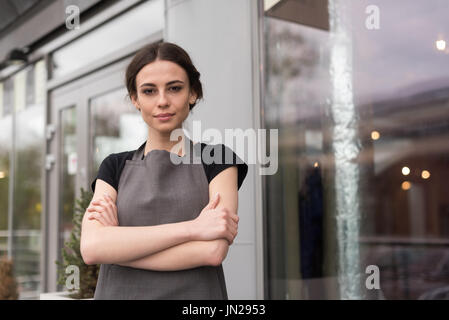 Portrait de femme propriétaire with arms crossed standing by coffee shop Banque D'Images