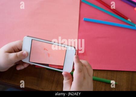 La main coupée de garçon photographiant le papier et crayons de couleur sur la table Banque D'Images