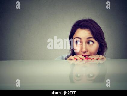 Worried woman regarder quelque chose d'oeil sous la table Banque D'Images