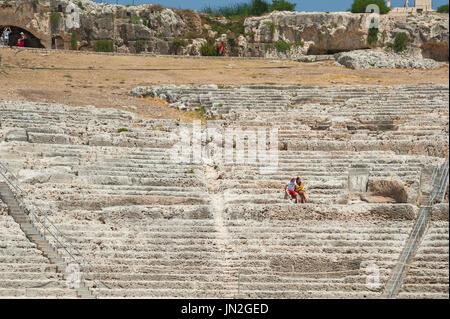 Sicile théâtre grec, un jeune couple assis parmi les ruines de l'amphithéâtre de l'ancien théâtre grec dans le parc Banque D'Images