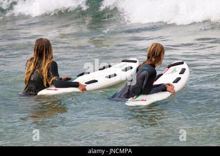 Deux filles de l'Australie dans l'océan au large de la plage de Sydney le port de combinaisons et se tenir sur leurs Banque D'Images