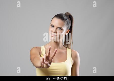Gorgeous sporty young female portrait montrant deux doigt main paix sur fond gris studio. Banque D'Images