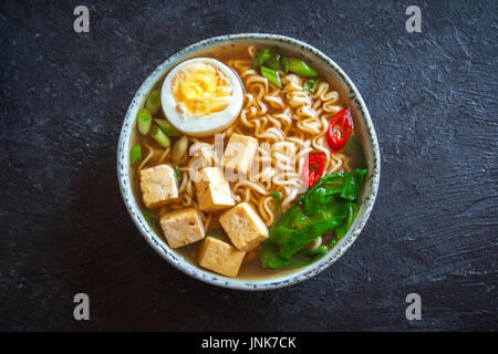Soupe ramen japonais avec du tofu et des oeufs sur pierre sombre arrière-plan. La soupe miso avec des nouilles ramen Banque D'Images