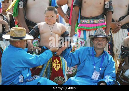 BEIJING, CHINE - un enfant wrestler grimaces comme une ceinture est trouvé trop court pour son ventre le premier jour de la Mongolie de trois jours du festival des sports traditionnels à Xilinhot Naadam en Chine, région autonome de Mongolie intérieure Le 28 juillet 2014. (Kyodo)