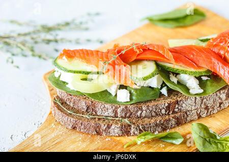 Sandwich au saumon fumé, légumes et fromage blanc sur une planche de bois. Banque D'Images