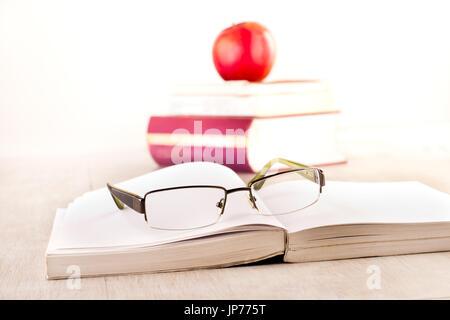 Close up de lunettes de lecture sur le livre ouvert sur 24 avec des tas de littératures et d'apple en arrière-plan Banque D'Images