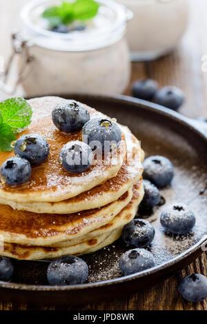 Smoothie aux bleuets biologiques sains en bocal de verre et crêpes au babeurre avec les baies fraîches sur la table Banque D'Images