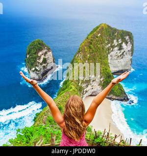 Vacances à la vie. Happy woman with a soulevé dans l'air du statif à vue. Regardez plage sous la falaise. Destination Banque D'Images