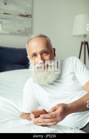 Les barbus man using smartphone alors que lying on bed Banque D'Images
