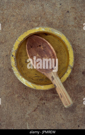 Petit plat en bois vide jaune battues avec beaucoup utilisé peu de cuillère en bois couché sur elle Banque D'Images