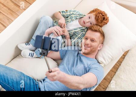 Smiling père et fils allongé sur un canapé et en tenant avec selfies smartphone, Family fun au home concept Banque D'Images