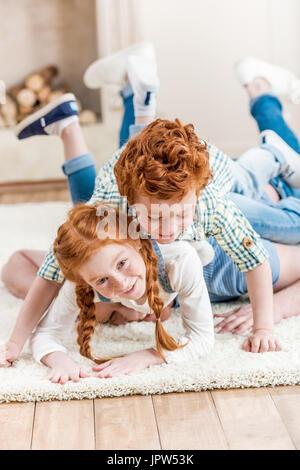 Adorable smiling redhead frères allongé sur le tapis et jouer ensemble, s'amuser en famille à l'accueil concept Banque D'Images