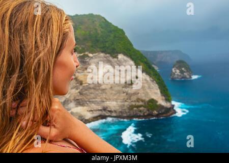 Style de vacances en famille.Woman stand à haute falaise sous ciel pluvieux. Regarder la mer avec plage de surf Banque D'Images