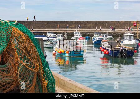 Bateaux dans le port avec les visiteurs sur le derrière de Cobb à Lyme Regis, dans le Dorset en Juillet Banque D'Images