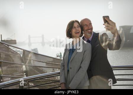 Enthousiaste, smiling business woman with camera phone selfies sur sunny urban bridge, London, UK Banque D'Images