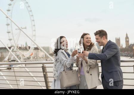 Enthousiaste, smiling friends toasting champagne urbain, sur le pont près de roue du millénaire, London, UK Banque D'Images