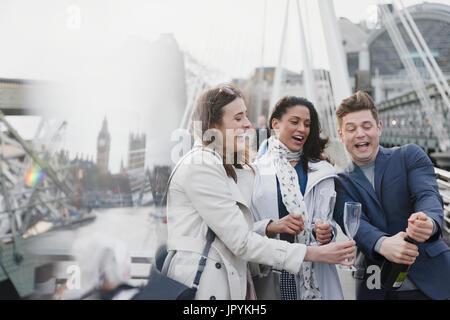 Les amis popping champagne, célèbre sur urban bridge, London, UK Banque D'Images