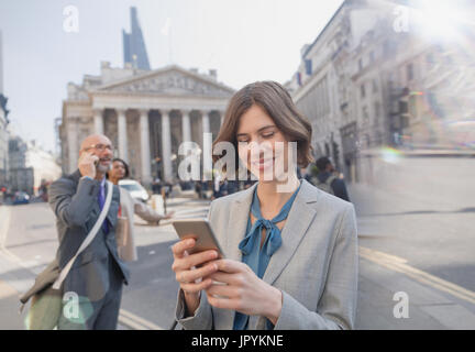 Businesswoman texting with cell phone on urban city Street, London, UK Banque D'Images