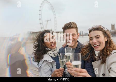 Portrait enthousiaste, smiling friends toasting champagne, près de roue du millénaire, London, UK Banque D'Images