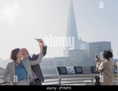 Couple d'affaires avec selfies téléphone appareil photo, London, UK Banque D'Images