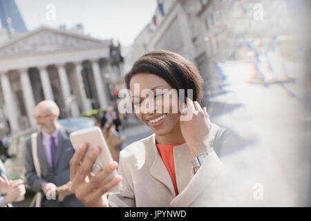 Smiling businesswoman prenant avec selfies téléphone appareil photo, London, UK Banque D'Images