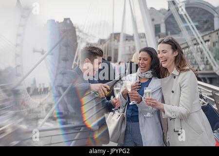 Amis souriant, heureux de célébrer, pouring champagne en ville, London, UK Banque D'Images