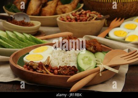 Nasi lemak, plat de riz savoureux malaisien avec du poulet frit, oeuf, arachide, d'anchois et de pâte de piment Banque D'Images
