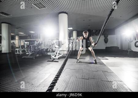 L'homme athlétique faire certains exercices de formation croisée avec une corde dans la salle de sport Banque D'Images