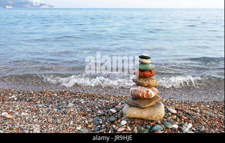 L'équilibre des pierres sur la plage au coucher du soleil. Concept de la paix et l'harmonie. Banque D'Images
