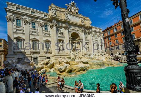 La fontaine de Trevi à Rome Italie sur une chaude journée d'été avec les touristes assis sur le bord Banque D'Images