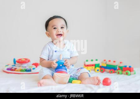 Adorable Bébé Garçon 9 mois asiatique assis sur le lit et jouer avec les jouets de couleur à la maison. Banque D'Images