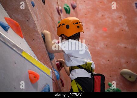 Déterminé boy practicing escalade in fitness studio Banque D'Images