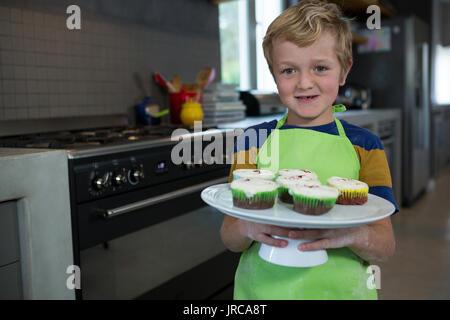 Portrait of boy holding plaque avec cupcakes dans la cuisine à la maison Banque D'Images