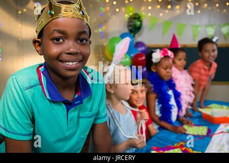 Portrait of boy wearing crown avec vos amis en arrière-plan pendant party Banque D'Images